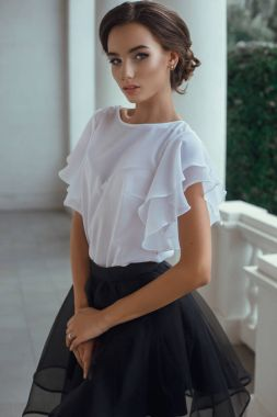 woman standing in blouse and skirt