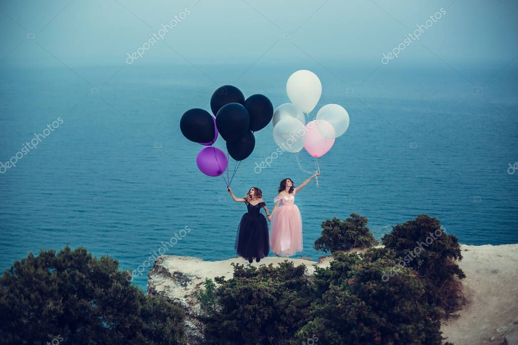 women in dresses holding balloons