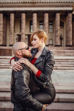 Beautiful couple on a cool motorcycle against Moscow