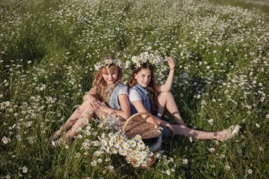 two cute teen girls in denim overalls walk in a daisy field. idea and concept of health, happy childhood, friendship