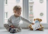 A gyerek az otthoni karanténban játszik az ablakban a beteg plüssmackójával, aki orvosi maszkot visel a vírusok ellen a koronavírus és influenza kitörésekor, azzal a tanáccsal, hogy maradjon otthon..
