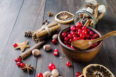 juicy cranberries in a plate and spice on wood table