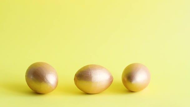 zlaté dekorativní vejce válcování a klepat navzájem žluté pozadí. Jarní prázdniny. Kopírovat mezeru, šablona mockup Velikonoční přání