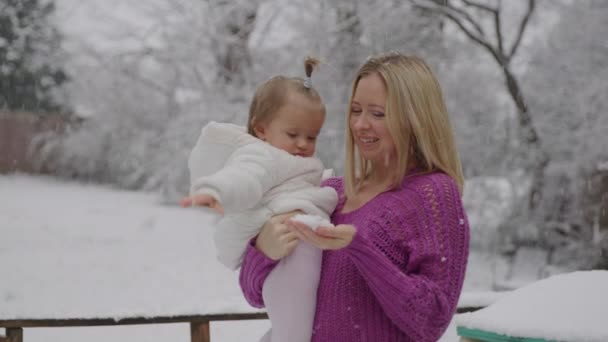 Young blond woman with her cute baby girl enjoying in snow park