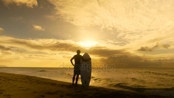 Fiatal szörfös vár tökéletes hullámok a naplemente a strandon