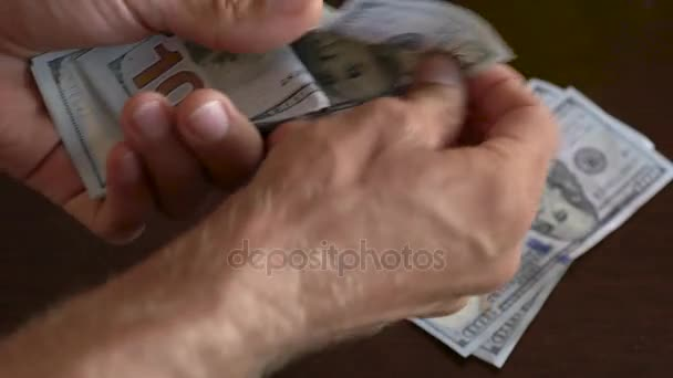 Close-up of a businessman hands counting hundred dollar bills at table