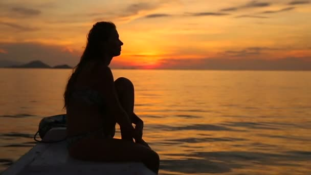 Sillouette dívka na lodi sledovat západ slunce