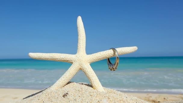 Láska svatební koncept zásnubní prsten a hvězdice na tropické pláži Oahu