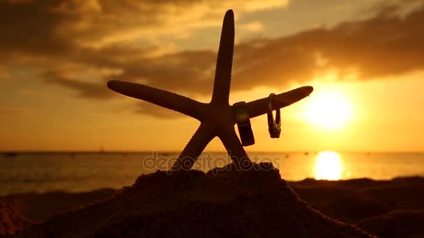 Cílový snubní prsteny a hvězdice na pláži při západu slunce milují koncept