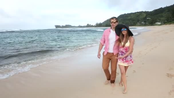 Loving young Caucasian couple holding hands walking together beach Oahu Hawaii