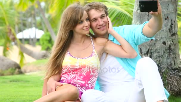 Smiling couple tourists taking self portrait with camera phone under palm tree