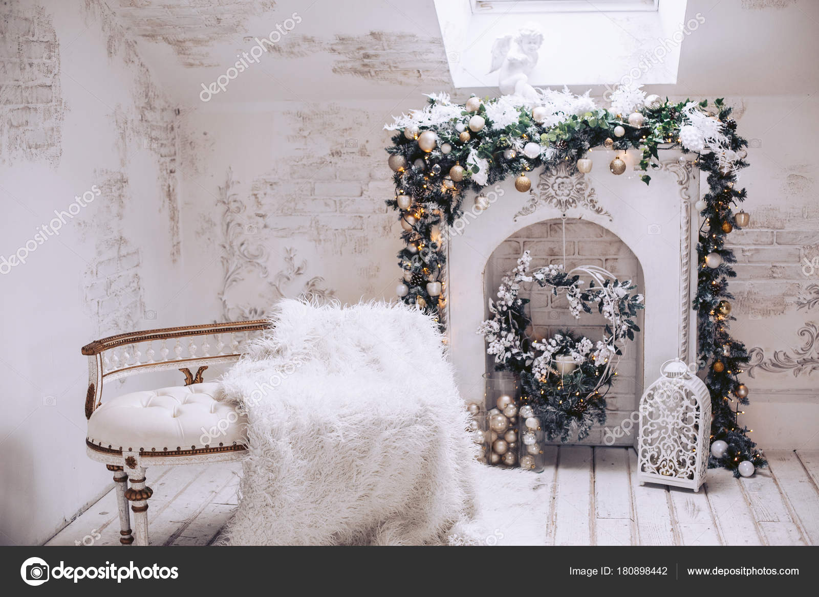 White exclusive sofa with gilding on the background of the fireplace. Christmas decorations from Christmas