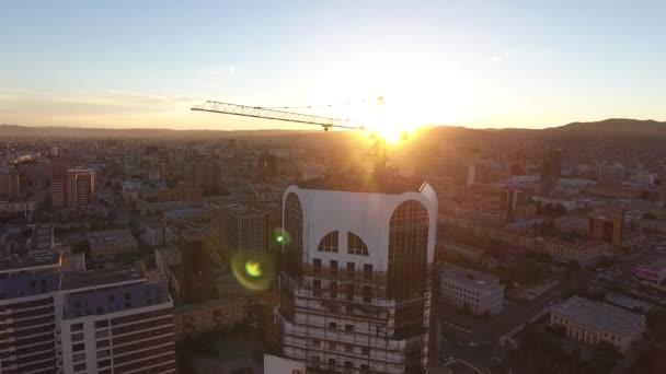 letecký bezpilotní snímek jeřábu na budově ve výstavbě v Mongolsku při západu slunce