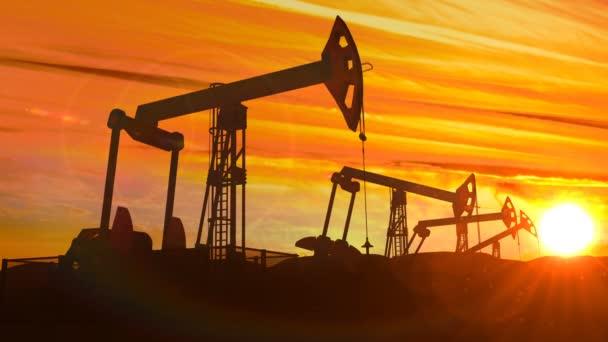 looped working oil pump jacks against dusk