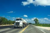 Vista frontale del semi-camion con rimorchio carico della guida su una strada.