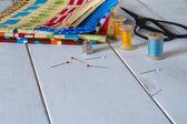 Barevné tkaniny s vintage nůžky, špendlíky, Svinovací metr a válcování bavlněného vlákna