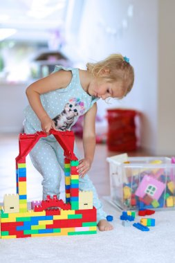 Little girl playing with construction bricks indoors