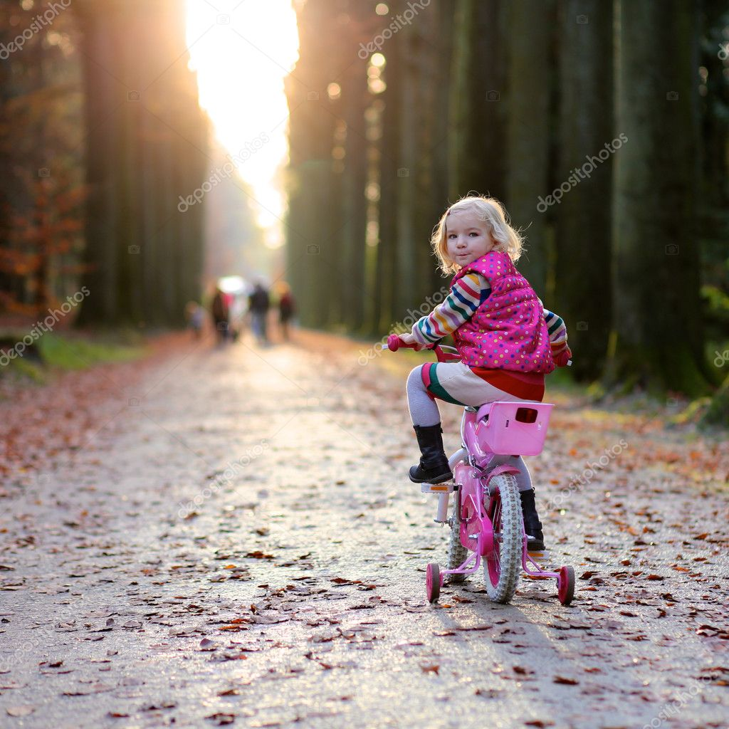Little girl enjoying sunny day in the forest or park