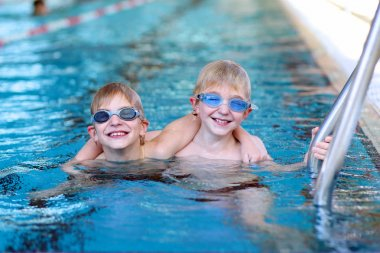 Two sportive kids swimming in the pool