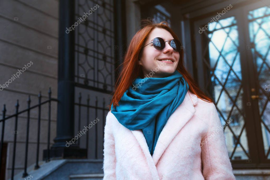 Red haired beautiful girl is walking by the street in a pink coat and blue scarf, with sunglasses.