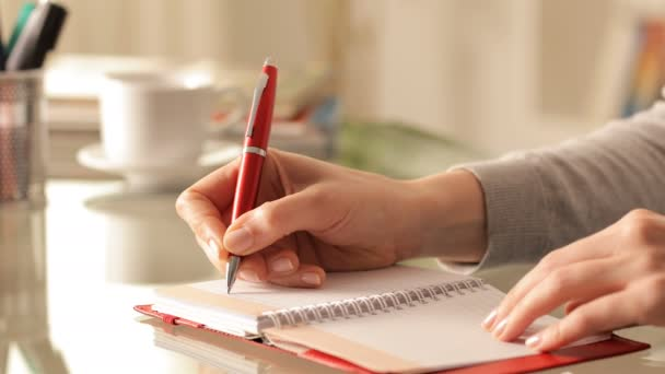 Close up of a woman hands writing on agenda on a desk at home