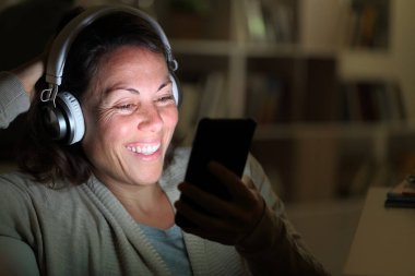 Happy adult woman with headphones listens music on smart phone with lighted screen in the livingroom at night at home
