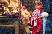 Kinder schauen sich auf Weihnachtsmarkt Süßigkeiten und Gebäck an