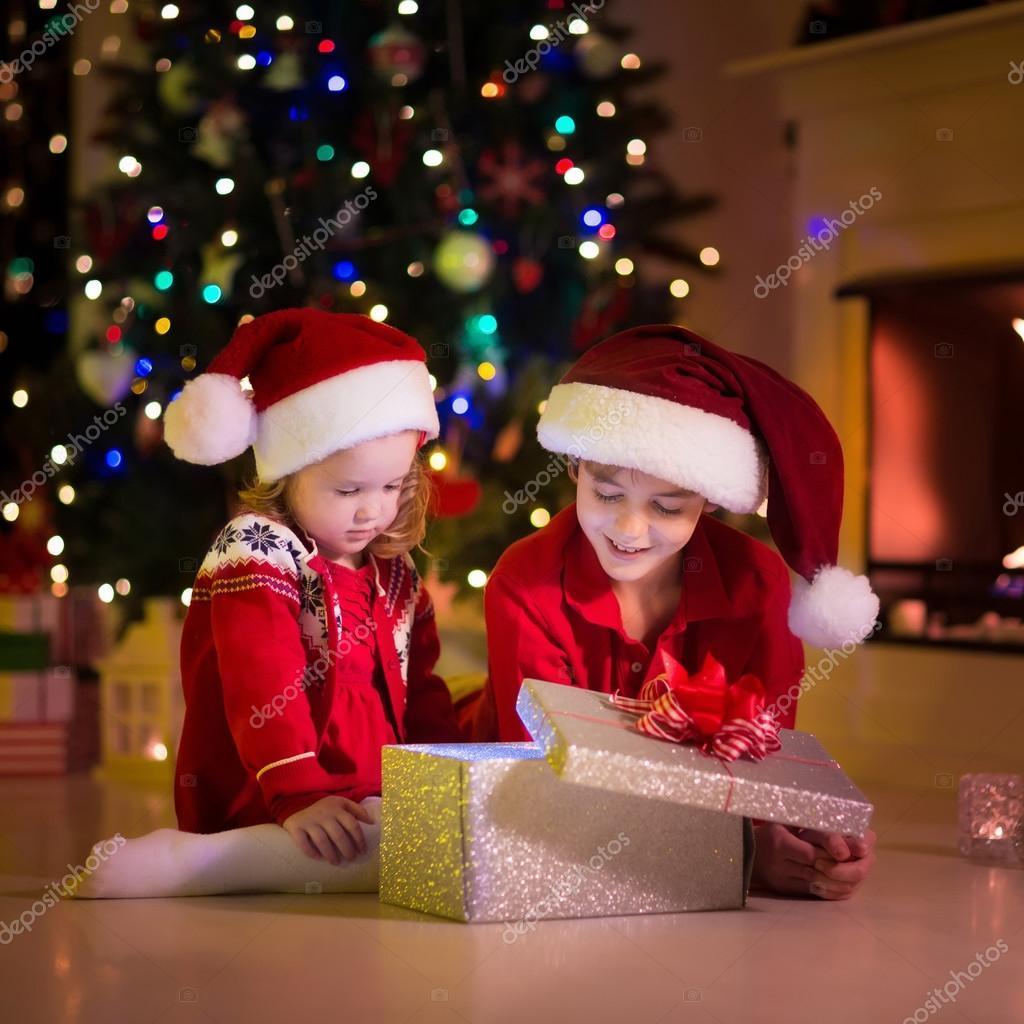 I Regali Di Natale Quando Si Aprono.Bambini Che Aprono I Regali Di Natale Al Camino Foto Stock