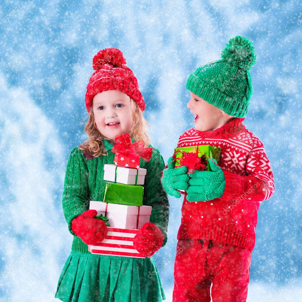 Kids with Christmas presents in winter park in snow — Stock Photo ...