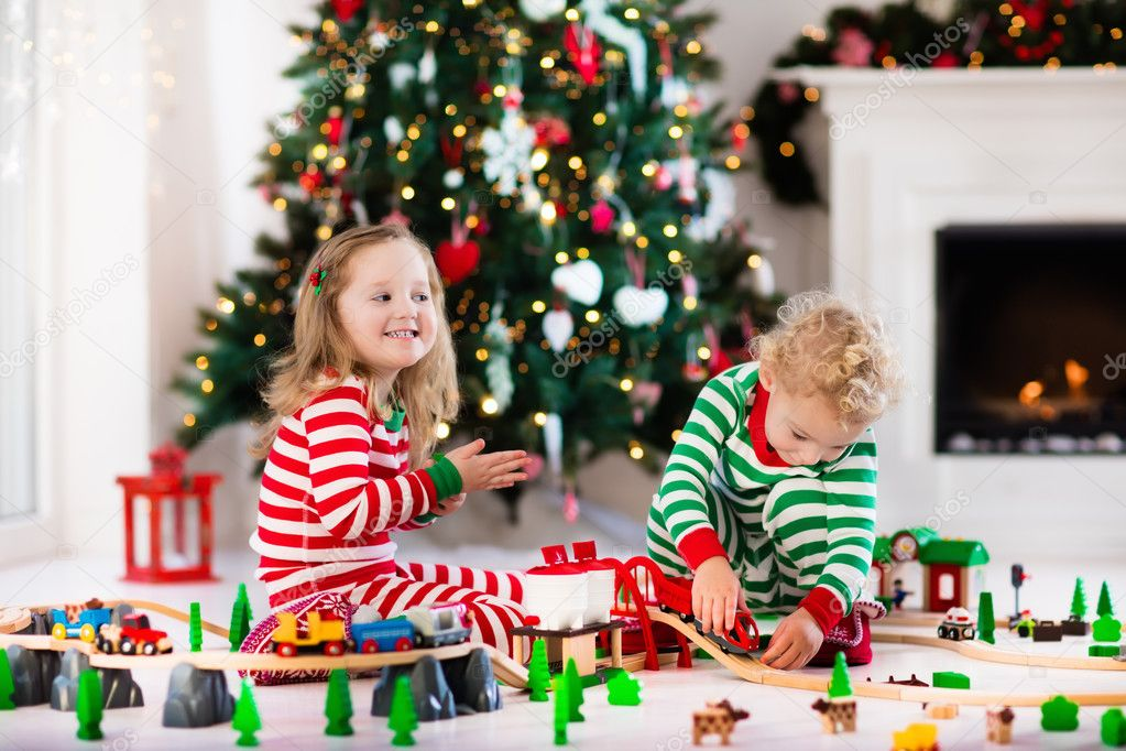 Kids playing with toy railroad on Christmas morning — Stock Photo ...