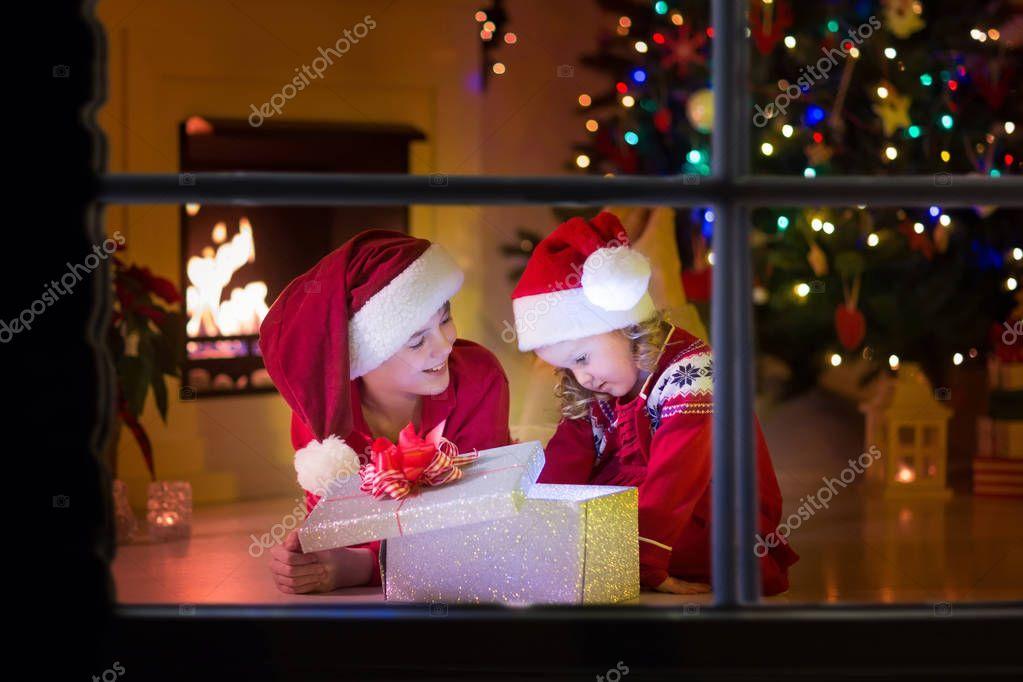 Traditionelle Weihnachtsgeschenke.Kinder öffnen Weihnachtsgeschenke Am Kamin Stockfoto Famveldman