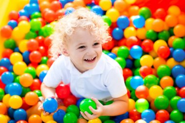 Happy laughing boy having fun in ball pit on birthday party in kids amusement park and indoor play center. Child playing with colorful balls in playground ball pool. Activity toys for little kid. stock vector