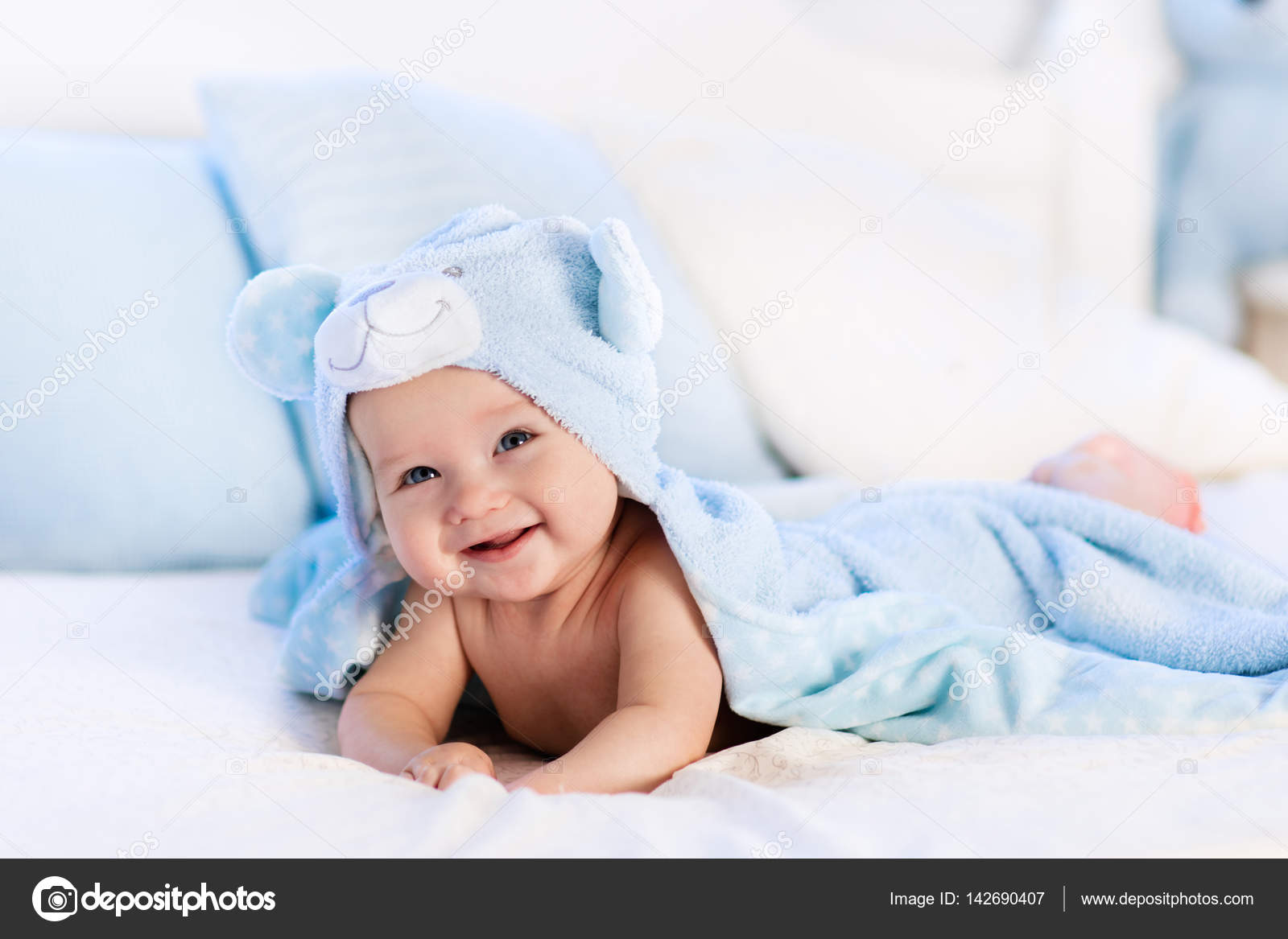 Baby in towel after bath in bed — Stock Photo © FamVeldman #142690407