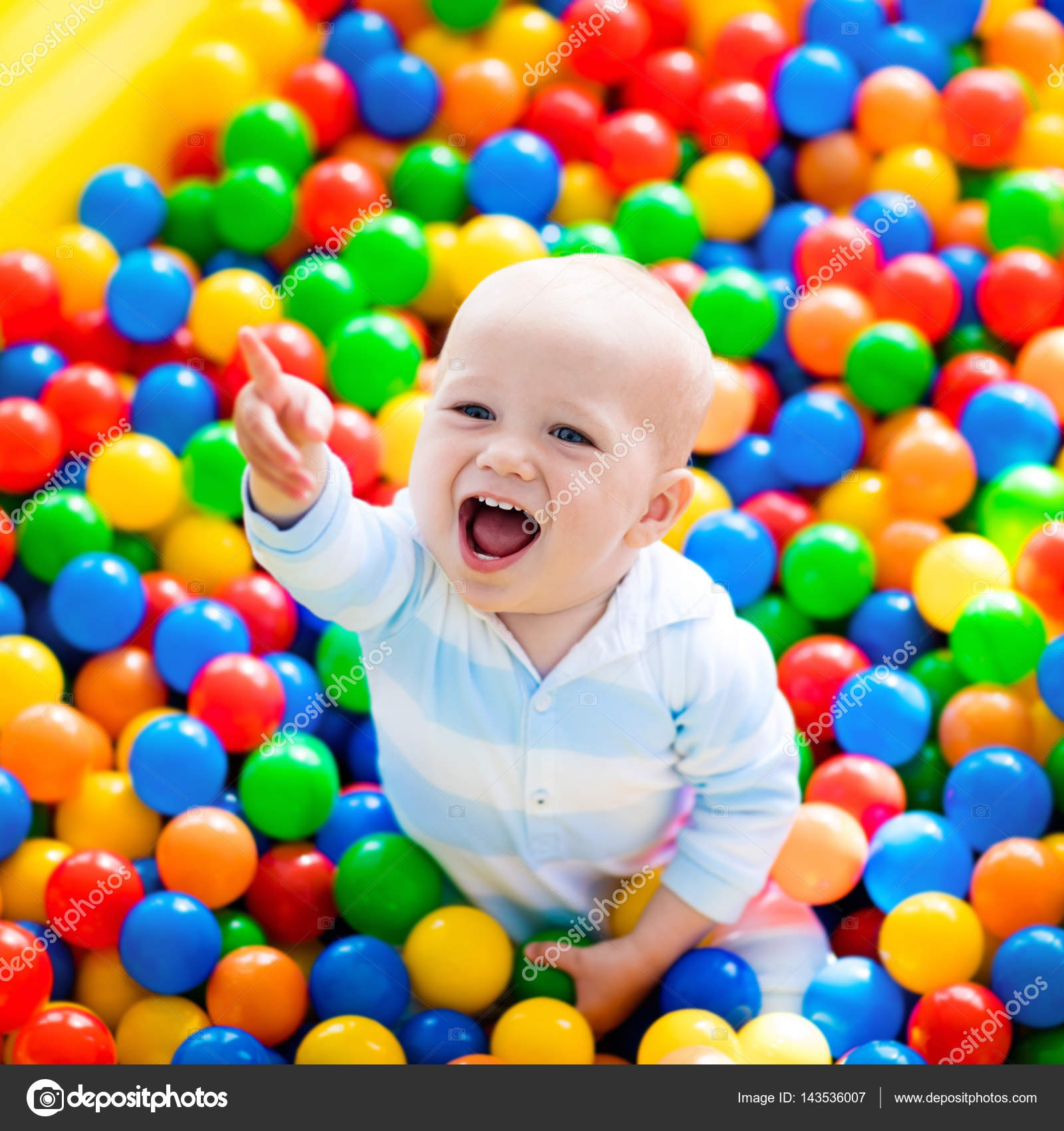 Child playing in ball pit on indoor playground Stock