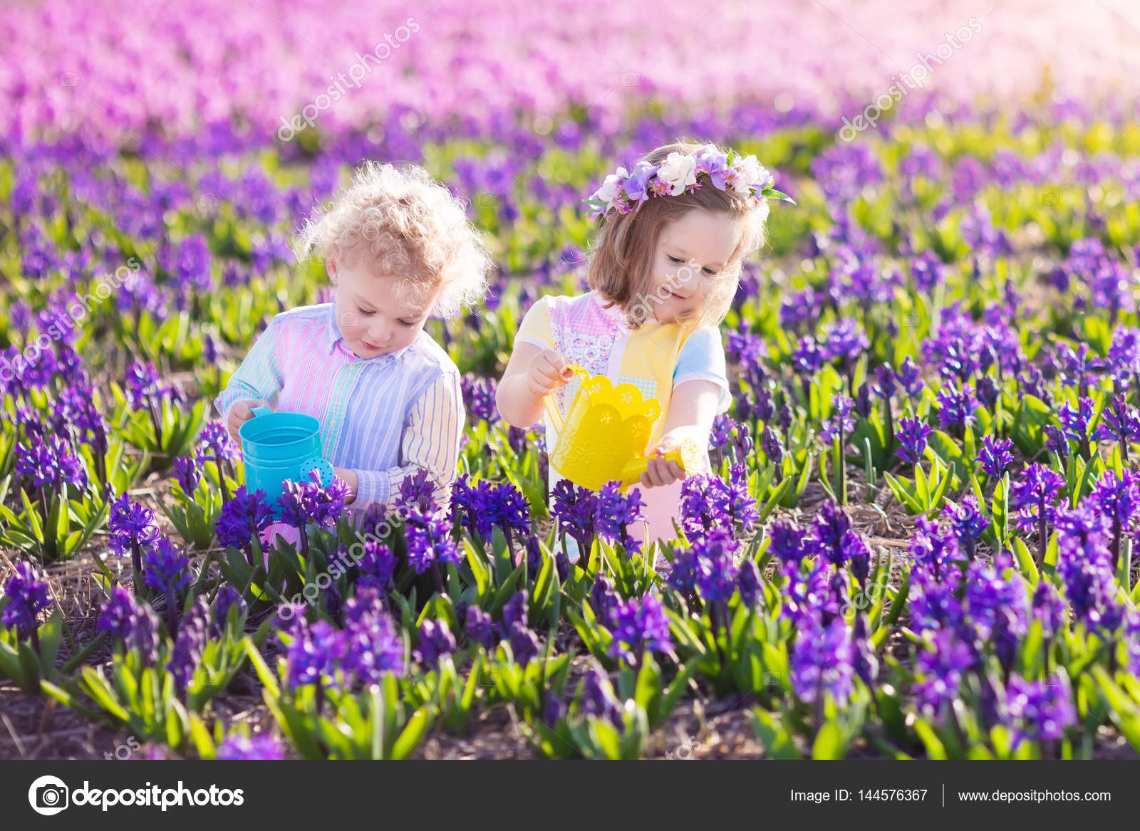 Kids Plant And Water Flowers In Spring Garden Stock Photo