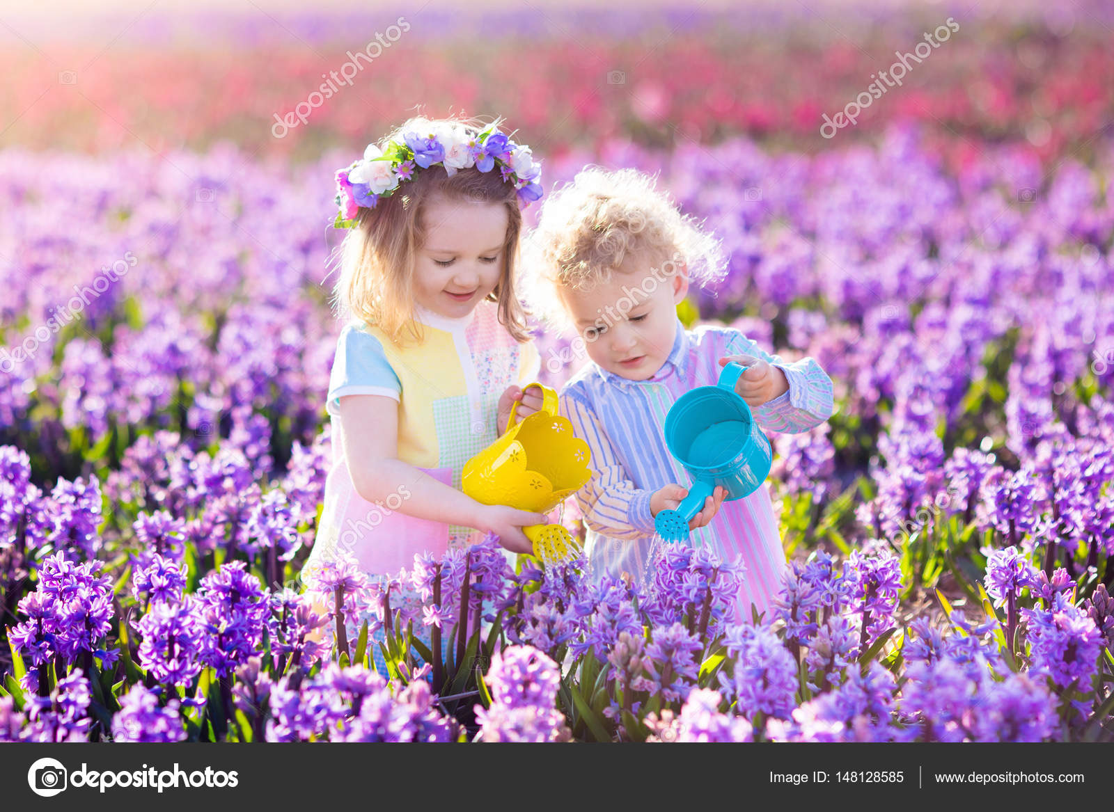 Kids plant and water flowers in spring garden stock photo children planting spring flowers in sunny garden little boy and girl gardener plant hyacinth daffodil snowdrop in flower bed gardening tools and water mightylinksfo Image collections