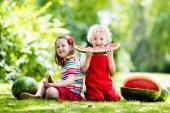 Fotografie Kinder essen Wassermelonen im Garten