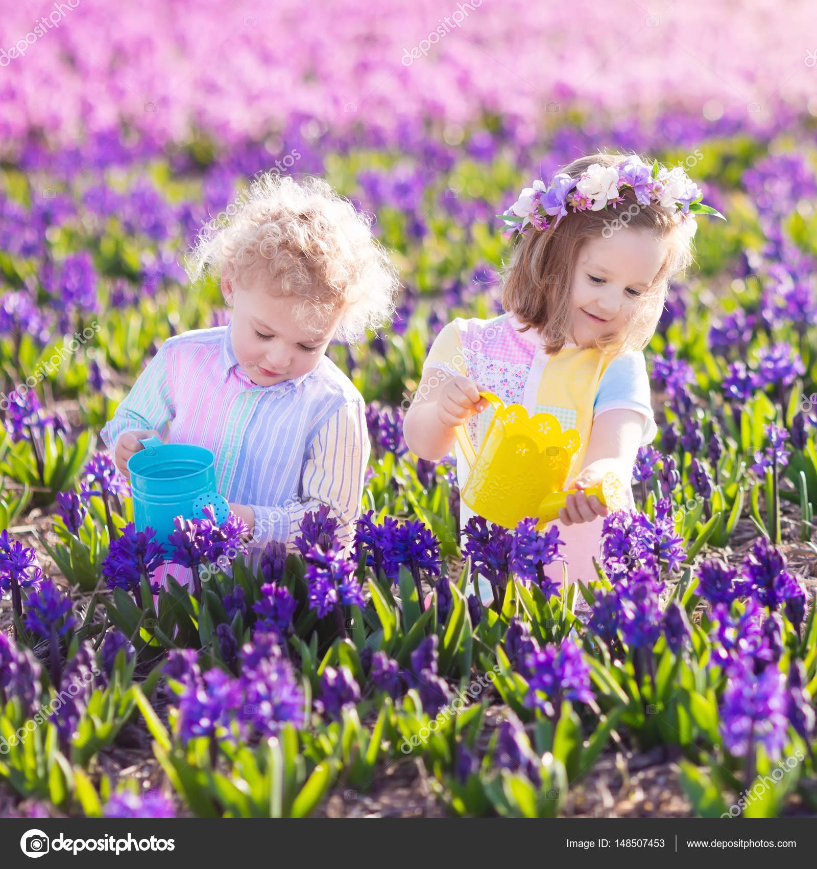 Kids plant and water flowers in spring garden stock photo children planting spring flowers in sunny garden little boy and girl gardener plant hyacinth daffodil snowdrop in flower bed gardening tools and water mightylinksfo Choice Image
