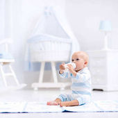 Baby Boy Trinkmilch in sonnigen Kindergarten