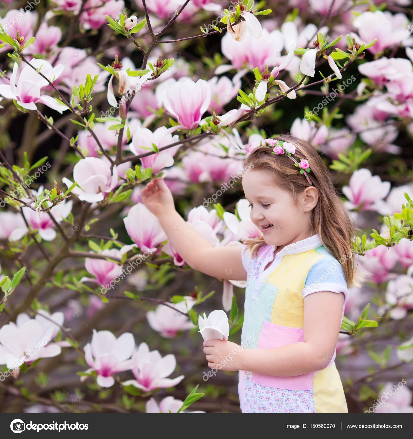 Child with magnolia flower little girl with flowers stock photo happy little girl in pastel color dress and flower crown playing under pink magnolia tree picking big flowers in blooming spring garden izmirmasajfo