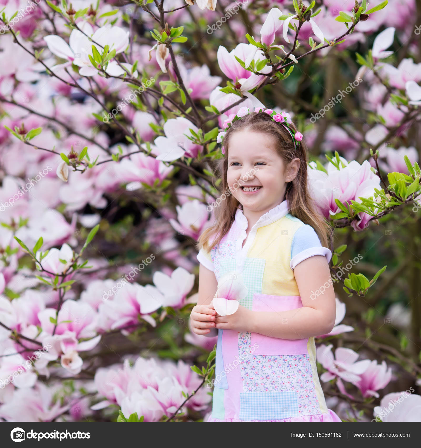 Child with magnolia flower little girl with flowers stock photo happy little girl in pastel color dress and flower crown playing under pink magnolia tree picking big flowers in blooming spring garden izmirmasajfo Gallery