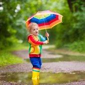 Dítě hrající v dešti pod deštníkem