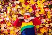 Děti v parku na podzim. Dítě s podzimní listy.