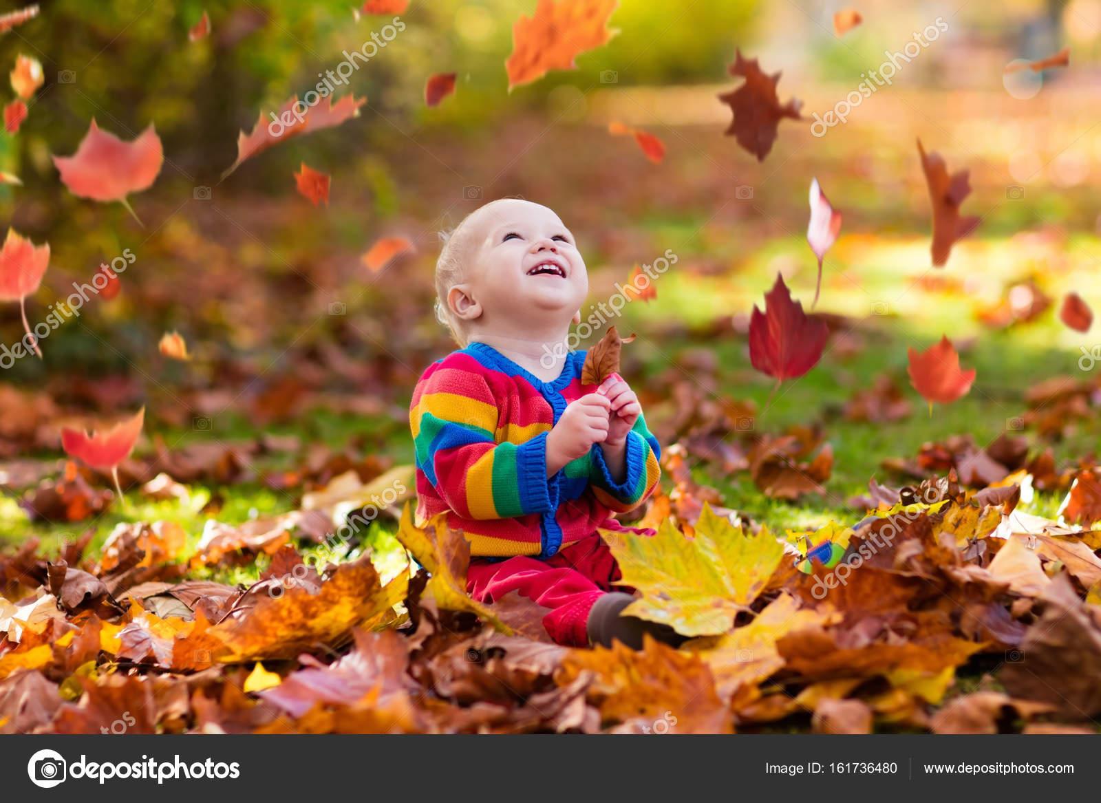 Enfants s amuseront dans parc automne. Enfants jetant les feuilles jaunes  et rouges. Bébé avec feuilles de chênes et d érables. Feuillage d automne. 8d7625c582a