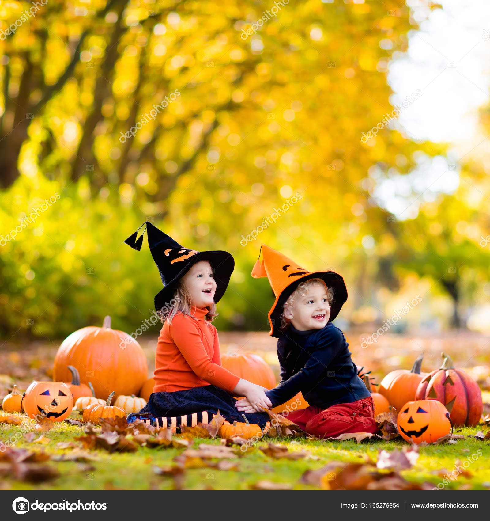 children in black and orange witch costume and hat play with pumpkin and spider in autumn park on halloween kids trick or treat