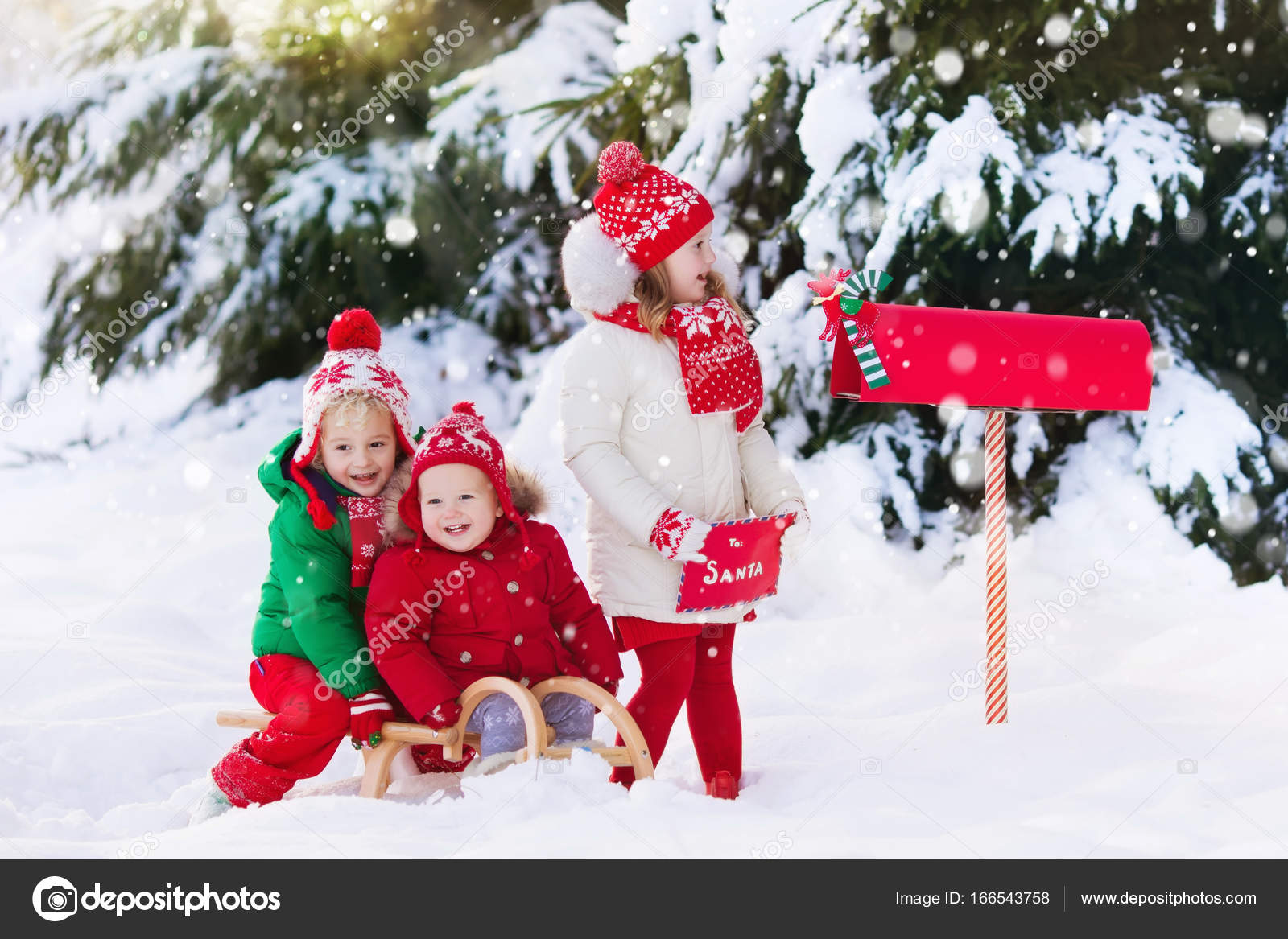 Children With Letter To Santa At Christmas Mail Box In Snow  Stock