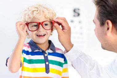 Child at eye sight test. Little kid selecting glasses at optician store. Eyesight measurement for school kids. Eye wear for children. Doctor performing eye check. Boy with spectacles at letter chart. stock vector