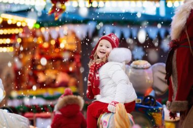 Child on Christmas fair. Kid riding Xmas carousel