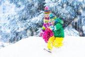 Fotografia Bambini che giocano nella neve. I bambini giocano allaperto in precipitazioni nevose di inverno