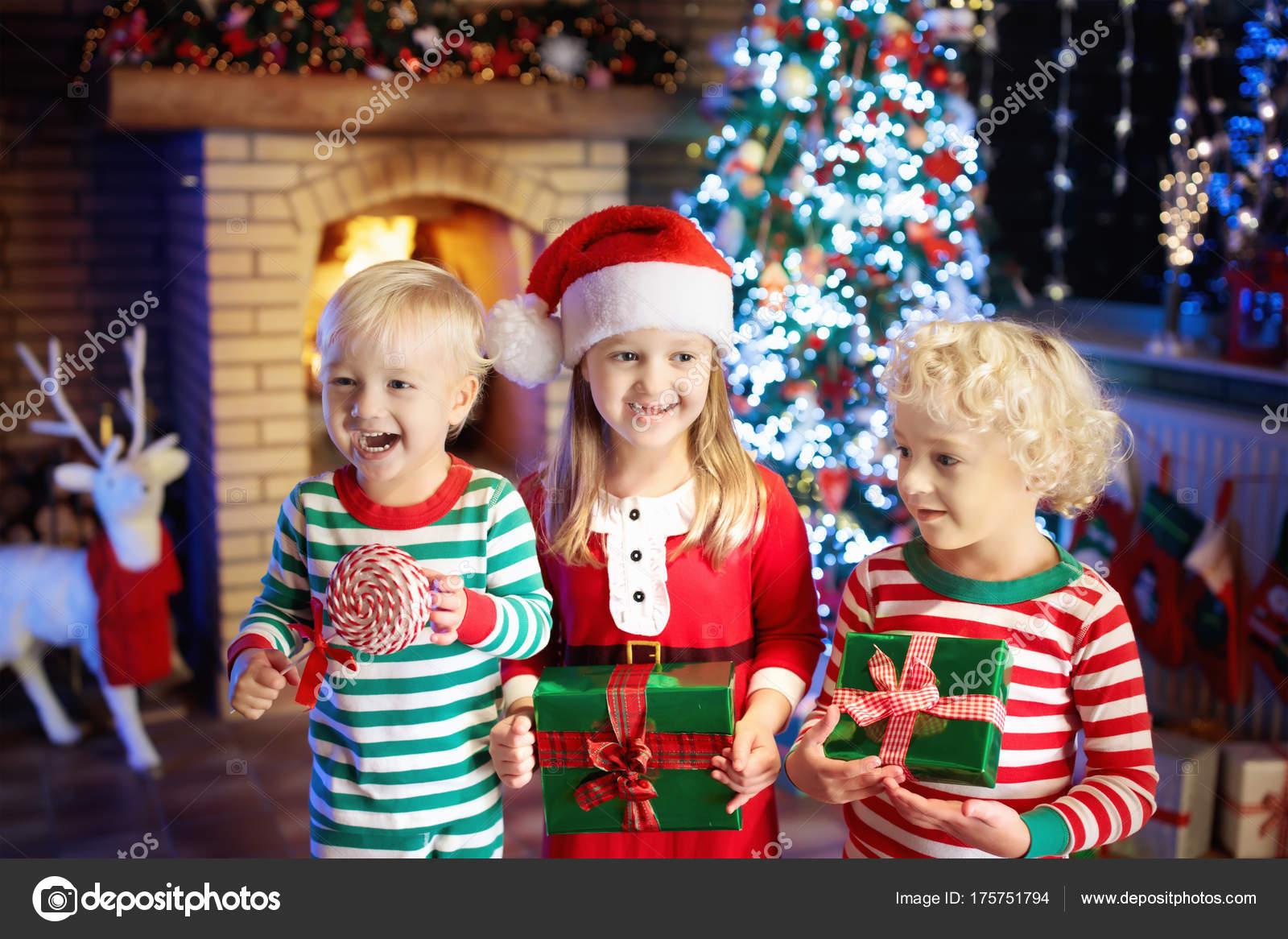 Child at Christmas tree. Kids at fireplace on Xmas — Stock Photo ...